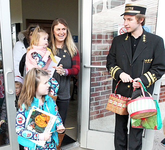 Candace H. Johnson-For Shaw Media Stephanie Moore, of Antioch and her children Keziah, 6, and Kaelin, 2, pass Austin Bates, 19, Lake Villa, assistant conductor, before getting on Antioch's North Pole Express Train to the North Pole.(12/19/17)