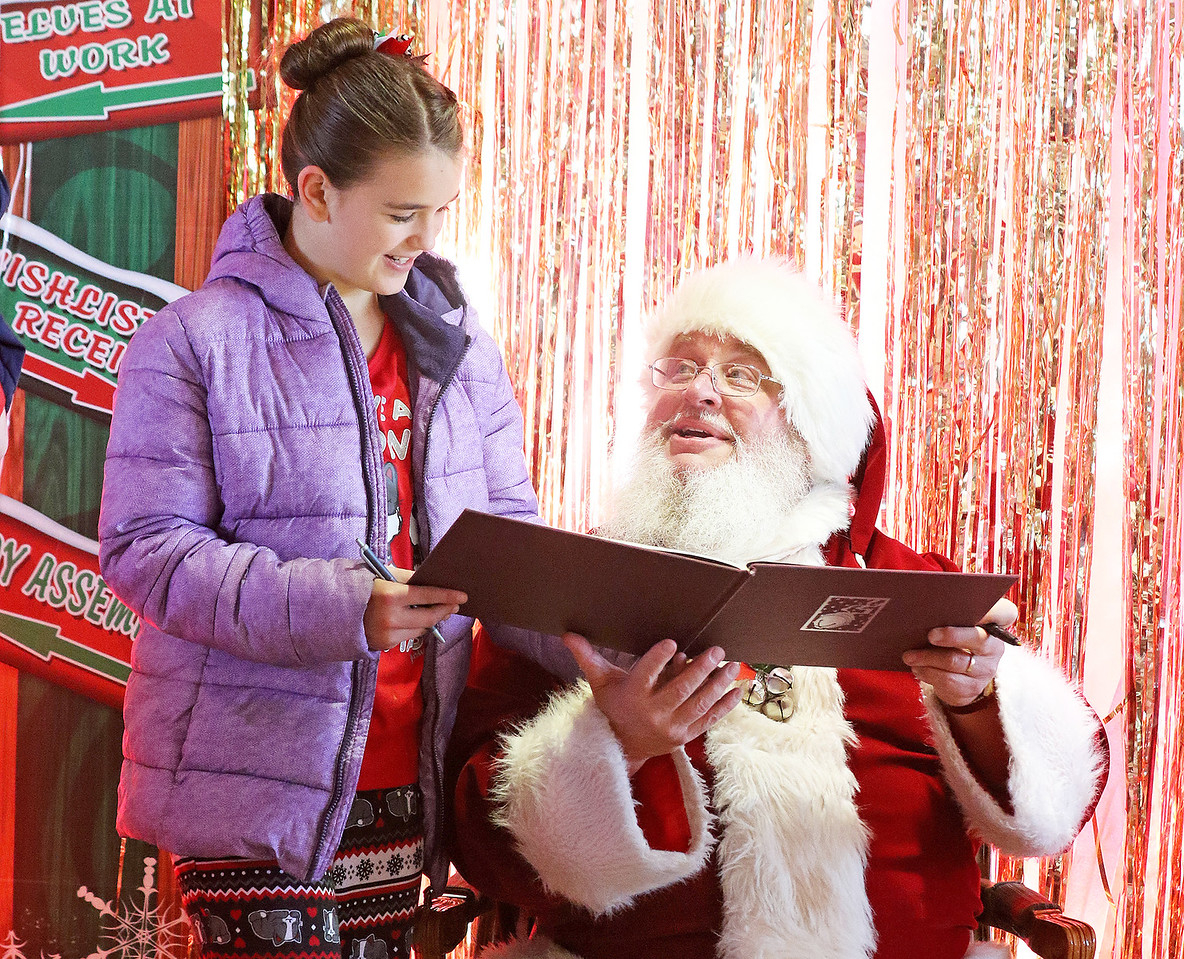 Candace H. Johnson-For Shaw Media Mycah Thompson, 10, of Antioch gets her copy of The Polar Express book autographed by Santa at the North Pole during Antioch's North Pole Express Train event.(12/19/17)