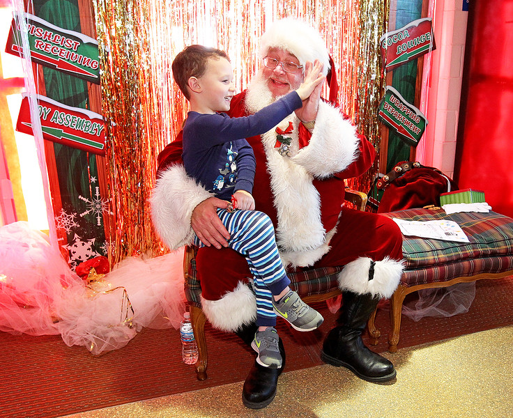 Candace H. Johnson-For Shaw Media L.J. Haley, 5, of Antioch gives a high-five to Santa at the North Pole during Antioch's North Pole Express Train event.(12/19/17)