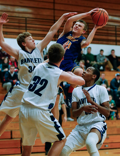 Zach Toussaint (14) from Johnsburg is fouled as he drives to the basket between Nicholas Wolf (34), Nicholas Wolf (34) and Byron Price (33) from Bartlett during the third quarter of the Hinkle Holiday Classic at Jacobs High School on Friday, December 22, 2017 in Algonquin, Illinois. The Hawks defeated the Skyhawks 63-51. John Konstantaras photo for Shaw Media