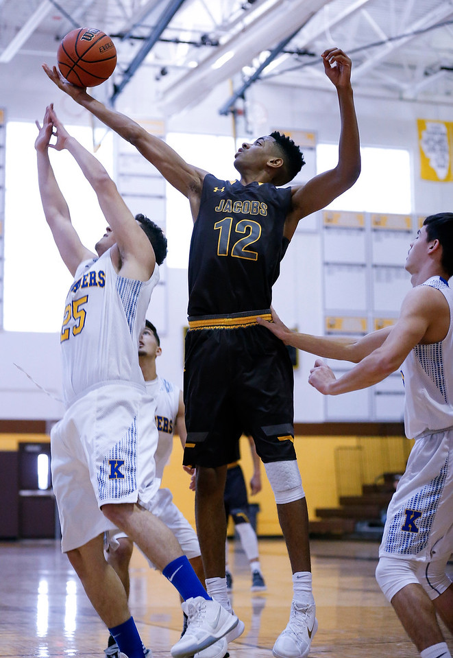 Kameron Mack (12) from Jacobs grabs a rebound over Mike Shell (25) from Kennedy during the second quarter of the Hinkle Holiday Classic at Jacobs High School on Saturday, December 23, 2017 in Algonquin, Illinois. The Golden Eagles defeated the Crusaders 71-31. John Konstantaras photo for Shaw Media