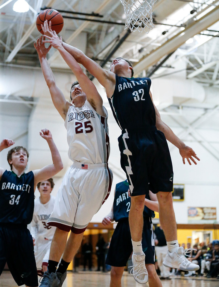 Colin Lamb (25) from Prairie Ridge and Ben Fisher (32) from Bartlett reach for a rebound during the fourth quarter of the Hinkle Holiday Classic at Jacobs High School on Tuesday, December 26, 2017 in Algonquin, Illinois. The Hawks defeated the Wolves 53-42. John Konstantaras photo for Shaw Media