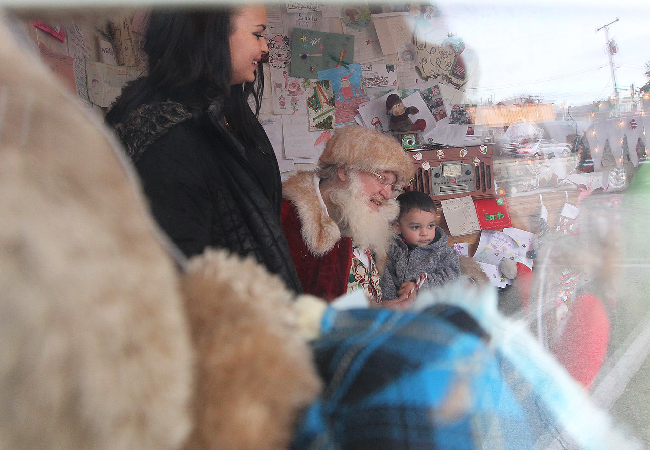 Candace H. Johnson-For Shaw Media Sarah Jensen, of Round Lake watches over her son, Brantley, 2, as he gets his picture taken with Santa by his father, Greg Cantu, of Harvard (not pictured) as seen through the window of the Santa House in Millennium Park in Fox Lake. (12/23/17)