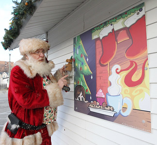 Candace H. Johnson-For Shaw Media Santa talks about the large painting of a little child waiting for Santa by artist Rebecca McConnell that hangs outside of the Santa House in Millennium Park in Fox Lake. (12/23/17)