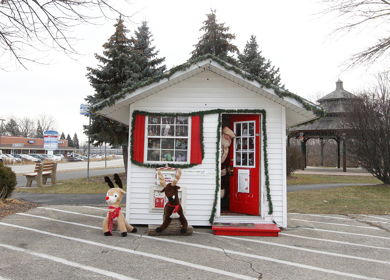 Candace H. Johnson-For Shaw Media Santa looks for visitors as he opens the door of the Santa House in Millennium Park in Fox Lake. (12/23/17)