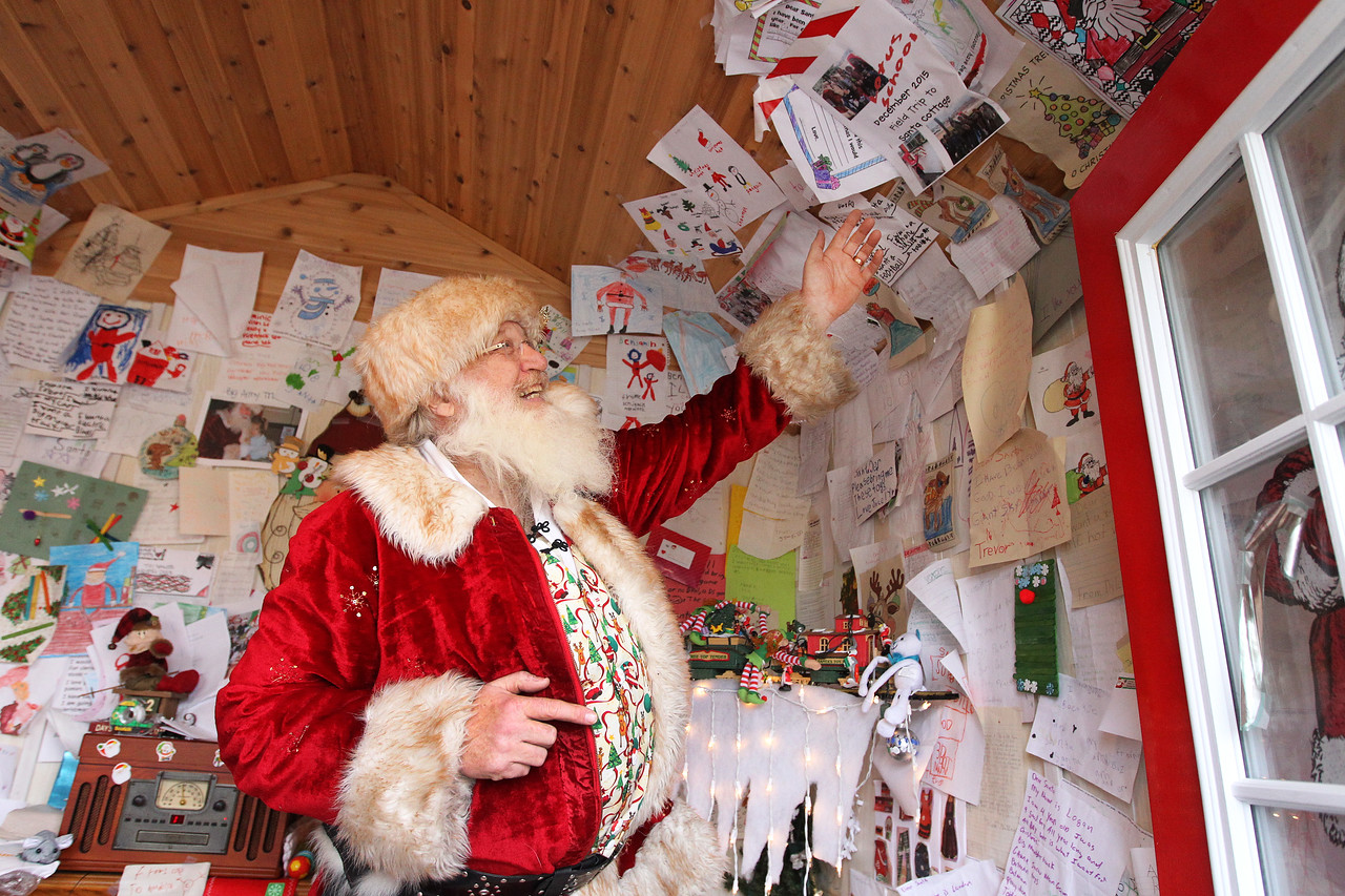 Candace H. Johnson-For Shaw Media Santa points out all of the letters and artwork he has received from children over the years that are on display at the Santa House in Millennium Park in Fox Lake. (12/23/17)