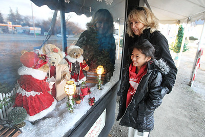 "Candace H. Johnson-For Shaw Media Cassidy Cupp, 8, of Burlington, Wis., and her grandmother, Pam Mastricola, of Lake Geneva, Wis., look at the oversized shadow box titled, ""Caroling, Caroling, through the Snow,"" at the Kringle's Christmas Village display in downtown Antioch. (12/23/17)"