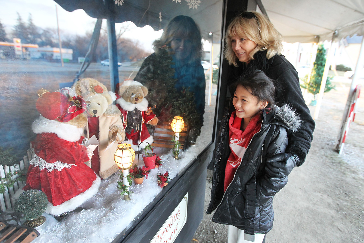 """Candace H. Johnson-For Shaw Media Cassidy Cupp, 8, of Burlington, Wis., and her grandmother, Pam Mastricola, of Lake Geneva, Wis., look at the oversized shadow box titled, """"Caroling, Caroling, through the Snow,"""" at the Kringle's Christmas Village display in downtown Antioch. (12/23/17)"""