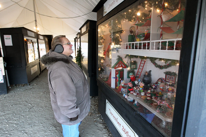 "Candace H. Johnson-For Shaw Media Pam Jacobs, of Gurnee looks at her favorite oversized shadow box titled, ""December 26th,"" at the Kringle's Christmas Village display in downtown Antioch. (12/23/17)"