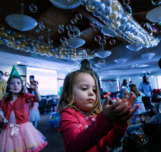 Nora Maroney, 3, catches bubbles during the Noon Year's Eve event at Lake in the Hills Village Hall on Sunday, December 31, 2017 in Lake in the Hills, Illinois. John Konstantaras photo for Shaw Media