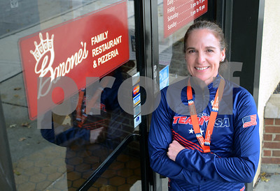 Barone's Family Restaurant and Pizzeria owner Dena Colie wears her medal and Team USA jacket Nov. 14, outside her eatery in Glen Ellyn. Colie representing Team USA in the 50 to 54 age group, placed 16th in the world and fifth on the USA team in her age group in the ITU World triathlon in Rotterdam, Netherlands. Mark Busch - mbusch@shawmedia.com