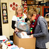 Batavia United Way board members Lisa Hillquist (left) and Cecelia Hoffman help sort gifts for families through the United Way's Adopt A Family program at Louise White Elementary School in Batavia. Over 100 families from throughout Batavia School District 101 were sponsored by community members and organizations to provide gifts and home essentials.