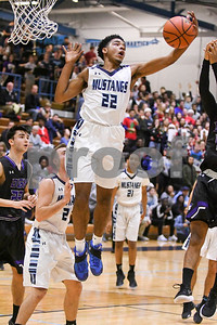 Downers Grove South's Wesley Hooker (22) rebounds the ball in the first quarter during the game against Downers Grove North Dec. 16 at Downers Grove South High School. David Toney - For Shaw Media