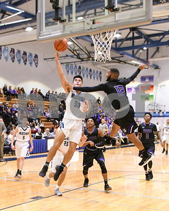 Downers Grove South's Patrick Shaughnessy (30) goes up for a layup in the third quarter while Downers Grove North Mychale Hyland (12) tries to defend during their game Dec. 16 at Downers Grove South High School. David Toney - For Shaw Media