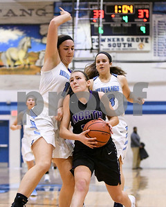 Downers Grove North's Julia Kramper (13) drives to the basket in the fourth quarter as she is gaurded by Downers Grove South's Jennifer Masello (11) during their game Dec. 16 at Downers Grove South High School. David Toney - For Shaw Media
