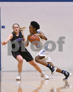 Downers Grove South's Jaylyn Grant drives to the basket as Downers Grove North Julia Kramper plays defense during their game Dec. 16 at Downers Grove South High School. David Toney - For Shaw Media