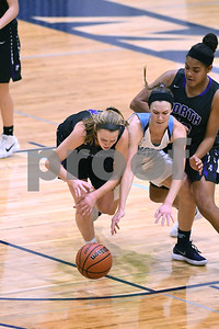 Downers Grove North's Julia Kramper (left) battles for the ball with Downers Grove South's Holly Lueken during their game Dec. 16 at Downers Grove South High School. David Toney - For Shaw Media