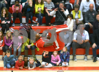 One of the Jesse White Tumblers flys in front of the crowd as they perform their routine in front of a packed house Dec. 1 at Timothy Christian. The school debuted their new gymnasium Friday with an evening that featured a boys and girls basketball game, the Jesse White Tumblers, and the National Anthem performed by Chicago Blackhawks Anthem singer Jim Cornelison. Mark Busch - mbusch@shawmedia.com