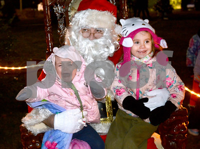 Shay Pistorius, 1, from Addison isn't to excited about meeting Santa as her sister Candace, 3, smiles Dec. 7 during the annual Tree Lighting at Wilder Park in Elmhurst. Mark Busch - mbusch@shawmedia.com