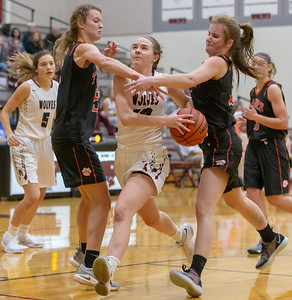 Prairie Ridge's Karly Statter splits Crystal Lake Central defenders Nora Ryan (L) and Emma Fleming (R) Tuesday, December 4, 2018 in Prairie Grove. Crystal Lake Central picked up the road victory 48-35.  KKoontz – For Shaw Media