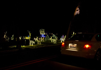 """Cars drive slowly down Bull valley road taking in all of the lights at Peter Messman's home Thursday, December 6, 2018 in Bull Valley. Messman has now teamed up with neighbor Ken Erickson and his famous """"White Deer House"""" making the experience even larger. KKoontz – For Shaw Media"""