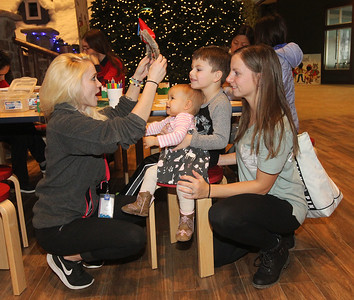Candace H. Johnson-For Shaw Media Meagan McMurray, of Round Lake Beach, an Ambassador of Fun, puts special wolf ears on Violet Caglianese, of Crestwood to celebrate her first birthday, as her brother, Dominic, 4, and mother, Nicole, watch at the Great Wolf Lodge in Gurnee.