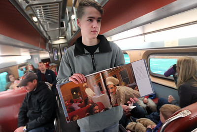 Candace H. Johnson-For Shaw Media Jack Mercer, 15, of Grayslake holds up The Polar Express book for everyone to see the pictures as the story was being read to families riding the Metra train to the North Pole (Fox Lake) to see Santa during the Grayslake Park District's Polar Express Storytime Train event. (12/2/18)