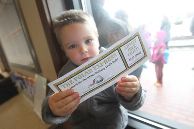 Candace H. Johnson-For Shaw Media Leo Lesinski, 3, of Grayslake holds up his golden ticket to board the Storytime Holiday Train as he waits in the Grayslake Metra Station with his mother, Sara, to take the train to the North Pole (Fox Lake) to see Santa during the Grayslake Park District's Polar Express Storytime Train event. (12/2/18)