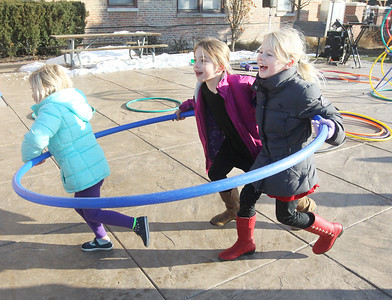 Candace H. Johnson-For Shaw Media Clover Carlin, 5, of Grayslake leads the way as she runs inside a hoola hoop with her sister, Keira, 8, and Kendra Abramson, 7, of Hainesville (in the middle) at Centennial Park during the Grayslake Farmers Market on Center and Whitney Streets in downtown Grayslake. Next Saturday, December 15th, the market is open from 10-2 pm, the fall market's last day of the season. (12/8/18)