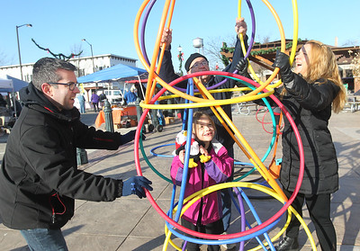 Candace H. Johnson-For Shaw Media Cheri and Chris Abramson, of Hainesville build a hoola hoop tower over their daughter, Kendra's, 7, head with the help of Ernie Garner, of Lake Villa (middle) at Centennial Park during the Grayslake Farmers Market on Center and Whitney Streets in downtown Grayslake. Next Saturday, December 15th, the market is open from 10-2 pm, the fall market's last day of the season. (12/8/18)