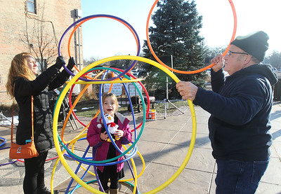 Candace H. Johnson-For Shaw Media Cheri Abramson, of Hainesville builds a hoola hoop tower over her daughter, Kendra's, 7, head with the help of Ernie Garner, of Lake Villa, who provided the hoola hoops and musical entertainment, at Centennial Park during the Grayslake Farmers Market on Center and Whitney Streets in downtown Grayslake. Next Saturday, December 15th, the market is open from 10-2 pm, the fall market's last day of the season. (12/8/18)