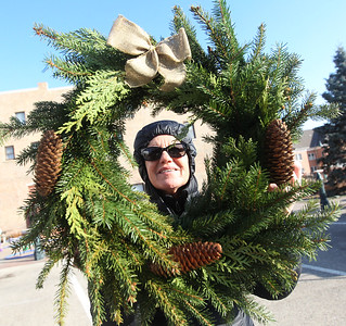 Candace H. Johnson-For Shaw Media Julie Jimenez, of Grayslake holds up and looks at a fresh holiday wreath for sale by Sol-ful blooms during the Grayslake Farmers Market on Center and Whitney Streets in downtown Grayslake. Next Saturday, December 15th, the market is open from 10-2 pm, the fall market's last day of the season. (12/8/18)