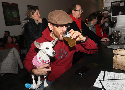 Candace H. Johnson-For Shaw Media Grant Epstein, of Grayslake sits with his dog, Dutchie, at the bar drinking some Dad Jokes beer during the Toy Drive & Pictures with Santa event at the Only Child Brewing Company Brewery & Taproom in Gurnee. (12/8/18)