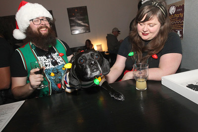 Candace H. Johnson-For Shaw Media Matt Muchowski, of Waukegan and his wife, Rachel Hewitt, sit at the bar with their dog, Gonzo, as they enjoy their beer during the Toy Drive & Pictures with Santa event at the Only Child Brewing Company Brewery & Taproom in Gurnee. (12/8/18)
