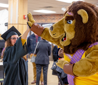 "Jessica Lynch ""High-Fives"" McHenry County College mascot Roary, Saturday, December 15, 2018 at the ceremony in Crystal Lake. Lynch received her Associates degree in the Arts. KKoontz – For Shaw Media"
