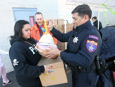 Candace H. Johnson-For Shaw Media Christina Soto, of Round Lake gets a ham and a turkey from Ricky Ignacio, an auxiliary deputy with the Lake County Sheriff's Office during the P.L.A.N. Holiday Ham & Christmas Toy Give-a-Way in Round Lake Beach. Micheal Brown, of Round Lake Beach, a volunteer and recipient, stood close by to help.(12/15/18)
