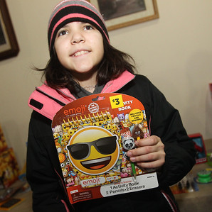 Candace H. Johnson-For Shaw Media Hailey Retzinger,11, of Round Lake Park shows off an emoji activity book she picked out during the P.L.A.N. Holiday Ham & Christmas Toy Give-a-Way in Round Lake Beach. (12/15/18)