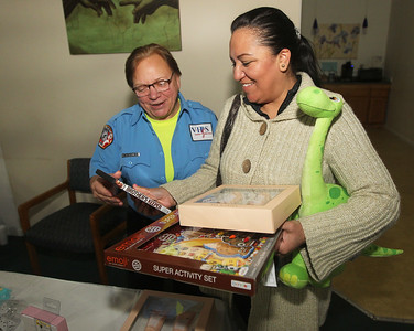 Candace H. Johnson-For Shaw Media Kim Kopoulos, of Lake Villa a volunteer with EMA, helps Agapita Velez, of Round Lake Beach pick out a video during the P.L.A.N. Holiday Ham & Christmas Toy Give-a-Way in Round Lake Beach. (12/15/18)