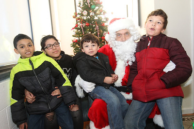 Candace H. Johnson-For Shaw Media Jonathan Benavidz, 8, of Round Lake sits with his sister, Rae, 16, and brother, A.J. Colon, 3, as they listen to what their brother, Kamden, 9, wants for Christmas as they visit with Santa during the P.L.A.N. Holiday Ham & Christmas Toy Give-a-Way in Round Lake Beach. (12/15/18)