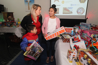 Candace H. Johnson-For Shaw Media Michele Pimpo, of Round Lake, assistant director, talks with Dylan Rico, 5, of Grayslake and his sister, Daisy, 12, as they pick out toys during the P.L.A.N. Holiday Ham & Christmas Toy Give-a-Way  in Round Lake Beach. (12/15/18)