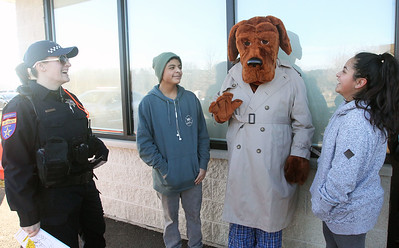 Candace H. Johnson-For Shaw Media Veronica Pesovic, an auxiliary deputy with the Lake County Sheriff's Office, watches as McGruff, the Crime Fighting Dog, waves hello to Jacob Garcia, 14, of Round Lake Beach and his sister, Elizabeth, 20, during the P.L.A.N. Holiday Ham & Christmas Toy Give-a-Way in Round Lake Beach. (12/15/18)