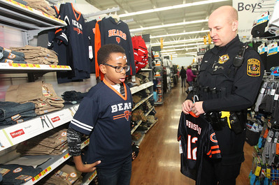 Candace H. Johnson-For Shaw Media Jediah, 12, of Lake Villa tries on a Chicago Bears jersey for size with the help of Brian DeKind, a Kildeer police officer, during Lake Villa's Shop with a Cop at Walmart in Round Lake Beach. (12/13/18)