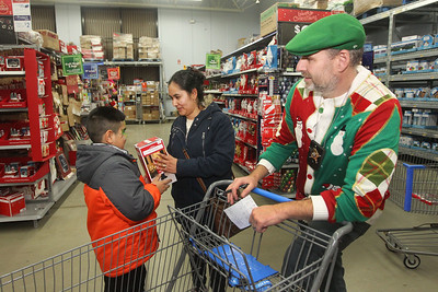 Candace H. Johnson-For Shaw Media Alonso Calderon, 8, of Round Lake Beach shows his mother, Blanca, a toy soldier he picked out with the help of Mike Janik, a retired Lake Villa police officer, during Lake Villa's Shop with a Cop at Walmart in Round Lake Beach. (12/13/18)