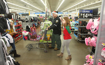 Candace H. Johnson-For Shaw Media Anthony Caliendo, a Lake Villa police officer, walks with Ryleigh Bock, 9, of Lake Villa through Walmart in Round Lake Beach to find things she wants to get during Lake Villa's Shop with a Cop. (12/13/18)