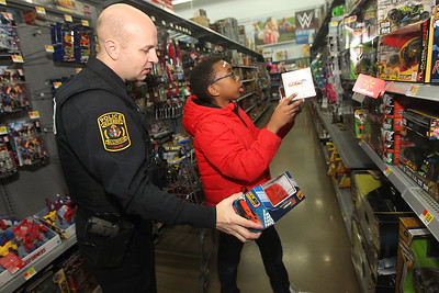 Candace H. Johnson-For Shaw Media Brian DeKind, a Kildeer police officer, helps Jediah, 12, of Lake Villa pick out a remote control car during Lake Villa's Shop with a Cop at Walmart in Round Lake Beach. (12/13/18)