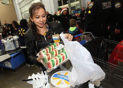 Candace H. Johnson-For Shaw Media Patty Ibarra, of Round Lake Beach, a OTC Department Manager, bags some holiday cookies for a child during Lake Villa's Shop with a Cop at Walmart in Round Lake Beach. (12/13/18)