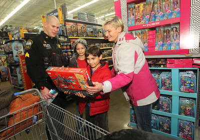 Candace H. Johnson-For Shaw Media Sgt. Erik Lindberg, with the Lake Villa police department watches Jeffery Estes, 12, of Lindenhurst and his brother, Kayden, 9, show their mother, Beckie, a Lego toy Kayden picked out during Lake Villa's Shop with a Cop at Walmart in Round Lake Beach. (12/13/18)
