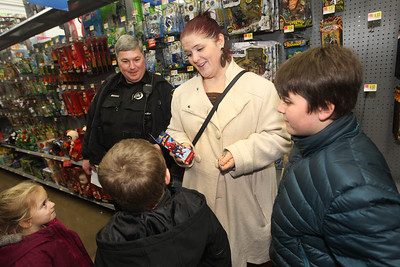 Candace H. Johnson-For Shaw Media Suzy Martin, of Lake Villa (center) talks to her son, Simon, 7, about a Spiderman toy he wants with the help of Mike Gardiner, a Lake Villa police officer, and his children, Madison, 6, and Logan, 11, during Lake Villa's Shop with a Cop at Walmart in Round Lake Beach. (12/13/18)