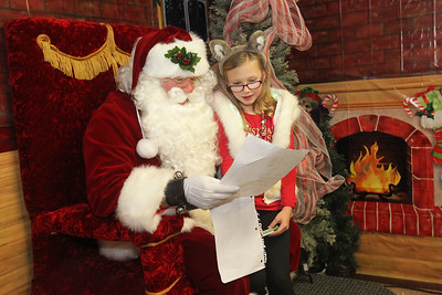 Candace H. Johnson-For Shaw Media Santa visits with Brooke Harvey, 10, of Fox Lake as she reads to him her Christmas list at Santa's Enchanted Village on Main Street in downtown Antioch. (12/15/18)