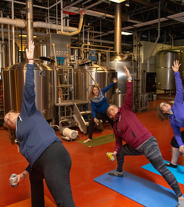 Beth Alberger (Left-Right) and Geri Schneff , and Amanda Storer learn stretches from instructor Laura Shultz during Yoga & Beer with Akasha held Wednesday, December 26, 2018 at the Crystal Lake Brewery in Crystal Lake. KKoontz – For Shaw Media